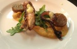 Charred octopus with smoked white bean puree, arugula with a preserved lemon vinaigrette, and cotechino sausage